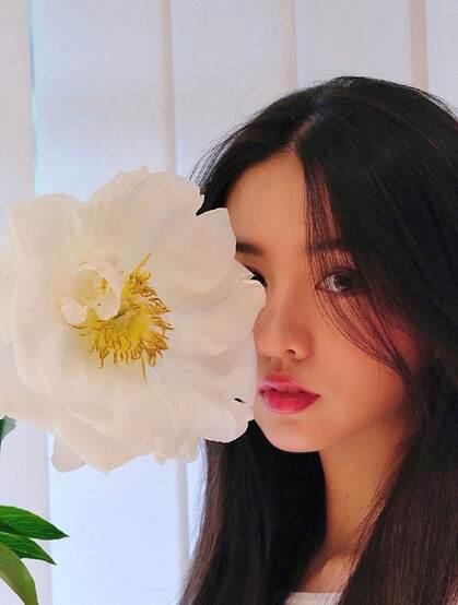 木村光希与花合影半遮娇颜,长发柔顺,难掩落落大方少女气质