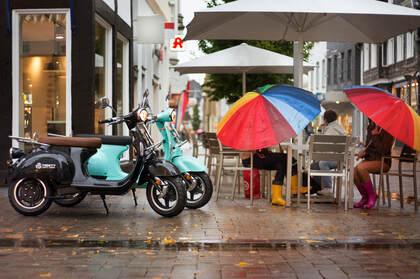 下雨的城市街头,在餐厅门前躲雨的路人场景桌面壁纸