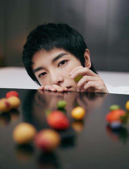 华晨宇全白look套装帅气个性在桌上玩小水果写真图片