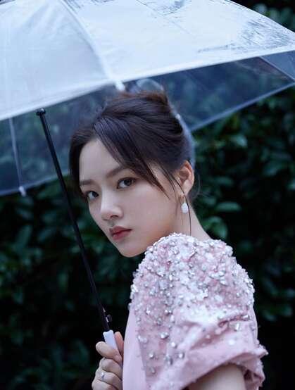 任敏身着粉裙手拿雨伞雨中漫步写真图片