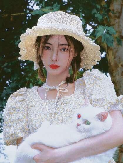 许佳琪头戴草帽,手抱猫咪,身穿小碎花裙户外清新写真图片