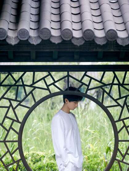 成毅一身白衣在绿意盎然的庭院中闲庭信步帅气写真照片